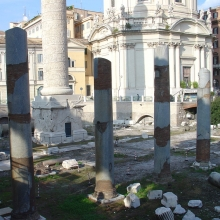 View from modern street level of the entrance side (southeast) of the pedestal of the Column of Trajan.  In the foreground are the gray granite columns of the Basilica Ulpia.