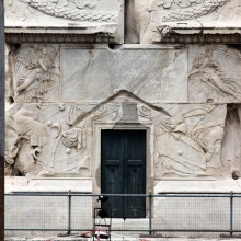 A view of the southeast side of the pedestal of the Column of Trajan. A pair of winged victories appear to support the dedicatory inscription over the door.  In the middle zone captured arms are represented in low relief.