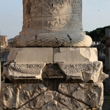 View of the lower elements of Trajan's Column in Rome with detail of the base of the Column, northwest side.  The lowest figural panel shows a scene of Roman ships being loaded along the shores of the Danube.