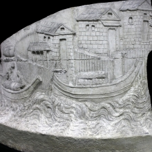 Scene 2/II: On the banks of the Danube, outside a fortified village, Roman soldiers load supplies.  An unmanned ship is stacked with dry goods.  The buildings in the background may be storehouses (horrea; Lepper and Frere (1988: 49).  