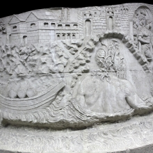 Scene 3/III: In the center, Danuvius, the personification of the River Danube, rises from the riverbed and sees a group of Roman soldiers moving through a gateway.