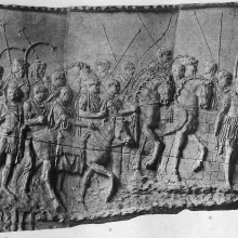 "Scene 5/V (plaster cast): Although Cichorius divided the river-crossing scene (#4) from this marching scene (#5), it seems likely that the action continues smoothly from bridge to land.  Although some have suggested that the figure just setting foot on enemy territory is Trajan himself, it seems more likely that the first appearance of the emperor is being reserved for the next scene.  Public domain image from <a href=""http://commons.wikimedia.org/wiki/Category:Trajan%27s_Column_-_Cichorius_Plates/"">Wikimedia</a>."