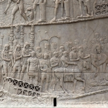 SCENE 5/V: Having crossed the pontoon bridges, the army continues its march in the direction of a tribunal and a council of war (Trajan, in his first certain appearance, can be seen seated on the far right). The window visible at the bottom of the photo marks the SE axis of the Column (aligned with the long axis of the forum).  From the Column in situ.  RBU2013.2098.