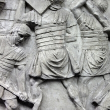 "Scene 127/CXXVII (detail): Close view of a soldier carrying a heavy block on his shoulder.  In reality, stone blocks would be too heavy to carry in this manner.  Richmond (1935) would argue that such scenes show sod, and not stone being carried.  However it may be that the artist was not overly concerned with depicting a ""realistic"" event.  The blocks look like heavy blocks of ashlar masonry.