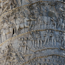 From the bottom of the image (Spiral 20, northwest side): Dacians kneel before the emperor in Scene 130. In the next scene a line of Romans crosses a pile bridge.  Above, in Spiral 21, valuable loot is loaded on mules (Scene 138) and Dacians assemble and move out in Scenes 139 and 140.From the Column in situ.  RBU 2013.3832.