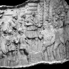 Scene 137/CXXXVII: Adlocutio Scene. Trajan, standing on a tribunal, addresses his troops; a walled Dacian town, protected by a gate and tower, forms the backdrop.  From casts 364-365, now in the Museo della Civiltà Romana, Rome. Compare Cichorius Pl. C, scene 137 and Coarelli Pl. 163. Ref: RBU2011.8271-137.