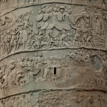 Scenes 125/CXXV and 134/CXXXIV:  Two scenes of Roman encampments on the southeast side of the Column.  The join between Column drums is clearly visible.  On the lower band we see Trajan within an undulating camp wall being greeted by his troops (perhaps a formal acclamation? Coarelli 2000: 198).  The quiet of the scene contrasts with the one directly above, where Dacian attackers, holding their shields over their heads for protection, attack a Roman fort.  Several of their number lie dead or wounded in the foreground.