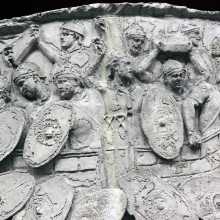 Scene 134/CXXXIV (detail): Close view of Roman defenders within the walls of their fort fending off a Dacian attack. The Romans' weapons include blocks of stone readied to be thrown upon the Dacian shields.  Timbered watchtowers are visible above the walls of the fort.