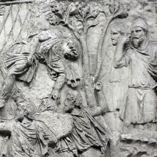 "Scenes 134-135/CXXXIV-CXXXV (detail): A Dacian warrior (left) falls back from the walls of a Roman camp after a failed attempt to scale the fortifications.  Another pileate Dacian, probably Decebalus himself, watches from a distance (right).  This is one of <a href=""http://www.trajans-column.org/?page_id=866"">six scenes</a> that are thought to represent the Dacian king. The tall tree between the two groups is considered a scene-divider by Cichorius.