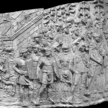 Scene 22/XXII (Spiral 3): Assembly of soldiers in anticipation of battle, including standard-bearers on the far right.   The setting is in a forest, as indicated by the line of trees at the top of the relief.