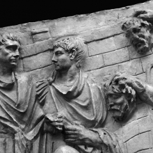 Scene 24/XXIV: Trajan (left) with an advisor is presented with severed heads of Dacian warriors held by Roman auxiliaries.