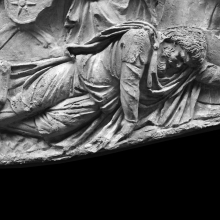Scene 24/XXIV: Detail of the first great battle scene. A fallen Dacian warrior.  Scene #24 represents the first images of dead or wounded Dacians. From a cast now in the Museo della Civiltà Romana, Rome. Compare Cichorius Pls. XVIII-XIX and Coarelli Pl. 23.  Ref: RBU 2011. 6984.