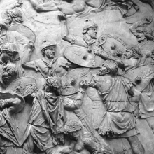 "Scene 24/XXIV: Segment of the first great battle scene. Jupiter joins the Roman side.A bearded Jupiter Tonans (the ""Thunderer"") appears in the sky to aid the Roman cause.  His right hand presumably held a thuderbolt.  His inclusion may refer to an actual thunderstorm that took place during the battle.  Included in the scene is a brilliant representation of a defeated Dacian semi-reclined at ground level.