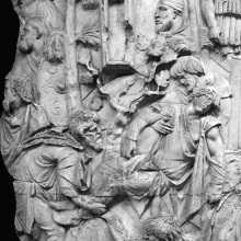 Scene 24/XXIV: The end of the first great battle.  The Dacians carry off their dead and wounded comrades.  The Dacian king, Decebalus, watches from the cover of a pine forest (upper right).  This is the first appearance of the Dacian king on the Column (his last appearance is the suicide scene of #145).