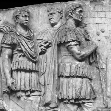 Scene 25/XXV: Trajan and advisors inspect a captured Dacian fort.  Not the the emperor (right) holds an inverted spear, a pose that suggests he has formally taken possession of Dacian territory (Coarelli 2000: 69).  Coulston notes that the upper half of the spear was added as a metal attachment, and was perhaps double-pointed like that in Scene 27 (Coulston 1990: 294).