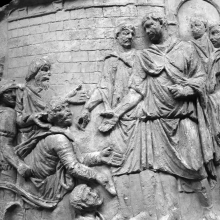 "Scene 46/XLVI: Trajan, about to embark by water (and hence the traveling garments) is petitioned by ""barbarians"" (Dacians?) who are escorted by Roman soldiers.  The range of hand gestures in the middle of the episode is notable.