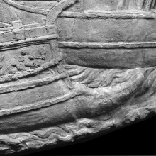 Scene 46/XLVI: The prow of a Roman warship.  The ramming beak (rostrum) is clearly visible.  The ship awaits the arrival of the emperor. Note the decorative detail of a putto riding on a dolphin.