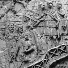 Scene 50/L: Trajan receives a group of legionaries who reach him by means of a wooden walkway.