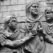 Scene 51/LI: Trajan greets a group of auxiliaries  A fortified camp forms the backdrop.