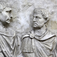 Scene 72/LXXII: Close view of Trajan and the officer who stands to his left (viewer right) as they are being presented with the severed heads of Dacians.