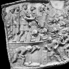 Scene 73/LXXIII: Trajan addresses his men within the walls of the camp (adlocutio).  In the foreground soldiers work with their axes (dolabrae) on rough timber - perhaps to prepare wood for artillery emplacements or to clear a line of fire.