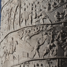 On the lower of two spirals, scenes 58/LVIII and 59/LIX: Trajan's bridge crossing is just visible to the left.  In Scene 59 Roman soldiers torch the planked buildings of the Dacians and the latter watch helplessly.  A draco standard flies in the background. Image from the Column in situ. RBU2013.3789.