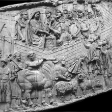 Scene 53/LIII: The second scene of Suovetaurilia on the Column of Trajan.  The emperor, velate, performs the initial sacrifice as the sacrificial animals are led around the walls of the camp. Either this is a different camp from that depicted in Scene 51 (Frere and Lepper 1988: 100), or it is the camp shown in the previous scene, now finished (Coarelli 2000: 99). From casts 132-34, now in the Museo della Civiltà Romana, Rome. Compare Cichorius Pl. XXXVIII, scene 53 and Coarelli Pl. 55.  RBU2011.7114
