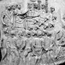 "Scene 54/LIV: Following the scene of sacrifice in Scene 53, Trajan addresses his troops (adlocutio). In the foreground, auxiliaries, then a group of legionaries in the middle and the standard-bearers forming the background.  Lepper-Frere suggest that the compact circular grouping of the scene may be influenced ""by the coin types showing such imperial addresses"" (1988: 100).  From casts 135-36, now in the Museo della Civiltà Romana, Rome. Compare Cichorius Pl. XXXIX, scene 54 and Coarelli Pl. 56.  RBU2011.7120."
