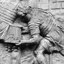 Scene 56/LVI: Legionaries at work clearing a forest and building a road.  Here a soldier dumps a load of rubble from a wicker basket.  His shield and helmet are propped up close by.  From cast 140, now in the Museo della Civiltà Romana, Rome. Compare Cichorius Pl. XL, scene 56 and Coarelli Pl. 58.  RBU2011.7125.