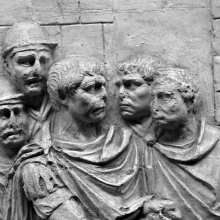 Scene 61/LXI: Close-up detail of Trajan (center, right profile), surrounded by four senior officers (the two behind him wear helmets). It has been proposed that he two bare-headed officers are meant to represent Licinius Sura and the Praetorian Prefect Claudius Livianus (Coarelli 2000: 106).