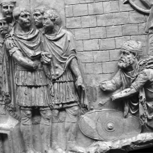 Scene 61/LXI: Trajan, surrounded by four senior officers (the two behind him wear helmets) receives a Dacian nobleman outside the walls of a Roman fort.  Coarelli suggests that the two bare-headed officers are meant to represent Licinius Sura and the Praetorian Prefect Claudius Livianus (2000: 106). 