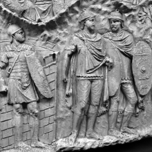 Scene 62/LXII: Detail of three Roman soldiers.  The legionary on the left guards the entrance to a Roman fort.  Two auxiliaries stand to the right.  