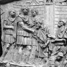 Scene 66/LXVI: Trajan, outside a fortress and flanked by officers, receives two Dacians wearing loose caps (pileati), the one closest to the emperor bends to take (and kiss?) his hand.