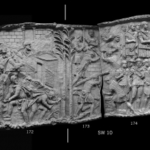Scenes 67-68/LXVII-LXVIII.  In scene 67 (casts 171-172) Dacians in the wake of the great battle of Scene 66 hastily fell trees and construct a palisade, behind which is a prominent building (a sanctuary? A flat-roofed gate tower? Cf. Lepper/Frere 1988: 105).  An imposing building in the background, on a rocky ridge, may be the palace of Decebalus at Sarmizegethusa (Coarelli 2000: 119), or an important fortified stronghold nearby.  In a scene with a parallel theme (68) marked clearly by a pair of trees, Roman legionaries work to construct a Roman fort.  Meanwhile (cast 174) the emperor, surrounded by his officers, receives a Dacian prisoner, one of the pileati, who is pulled towards the emperor by flanking auxiliaries. From casts 171 - 175, now in the Museo della Civiltà Romana, Rome. Compare Cichorius Pls. XLVIII-XLIX scenes 77-68 and Coarelli Pls. 75-76.  Ref: RBU2011.7166-composite.