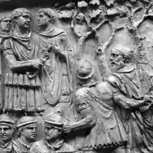 Scene 68/LXVIII: Trajan, surrounded by four officers, receives a Dacian prisoner of noble rank (a pileatus).