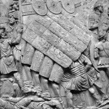 Scene 71/LXXI:  Detail of a Roman testudo formation.  Legionaries create a unified shell of shields above their heads and around their bodies as they attack a Dacian stronghold.
