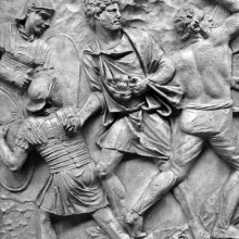 Scene 72/LXXII: Alongside the legionaries an allied fighter prepares to throw a rock.  He is probably armed with a sling, although the stance suggests nothing less than rock-throwing.