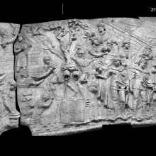 Scenes 19/XIX-21/XXI (Composite view). Scene 19: A bridge-building scene (note the legionary crouching in the foreground holding a diagonal brace).  The two tall trees at the top of the relief indicate an independent scene here.  Scene 20: Fort construction.  The fort is being constructed from blocks of sod.  Scene 21: In the background we see tents within a fort with walls of sod (despite the improbably arched forms seen in the walls.  Two sentries guard the encampment while riders depart over a wooden pile bridge. Compare Cichorius Plates XV and XVI (Scenes 19-21).  Casts in the Museo della Civiltà Romana. Ref: RBU2011.6964composite