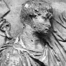 Scene 6/VI: A detail of Trajan in right profile, seated upon his tribunal and reviewing his troops.  This is the first certain appearance of the emperor on the Column. Cast in the Museo della Civilta' Romana, Rome. Compare: Cichorius P. IX, scene 6. Ref: RBU2012.9876.