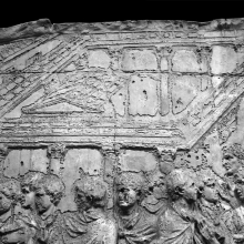 Scene 81/LXXXI (detail): in the background of a harbor town scene we see the top of a temple within a colonnaded Corinthian portico, which is covered by a walkway along its four sides. From casts 214-215, now in the Museo della Civiltà Romana, Rome. Compare Cichorius Pl. LX (Scene 81) and Coarelli Pl. 95.  RBU 2011.8082.